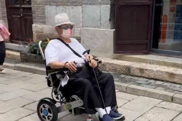 69歲洪金寶坐輪椅逛古鎮,需兩人攙扶上台階